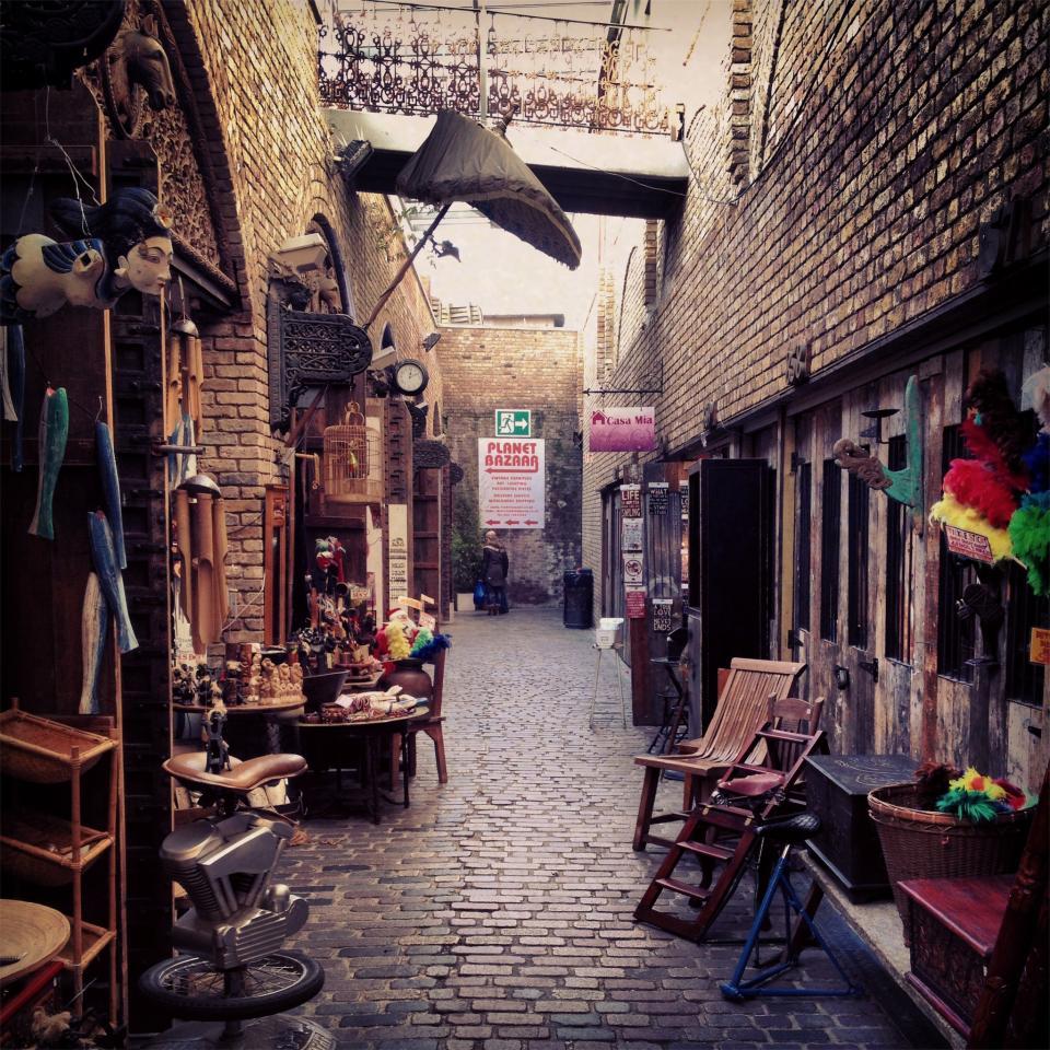 stores shops merchandise market goods cobblestone chairs birdcage bazaar alley