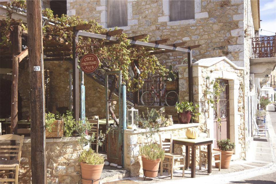 tables stones sidewalk restaurant pots plants greek flowers entrance chairs