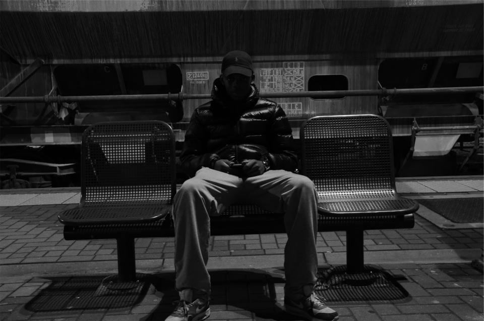 young sitting people pants man jacket hat guy chairs blackandwhite
