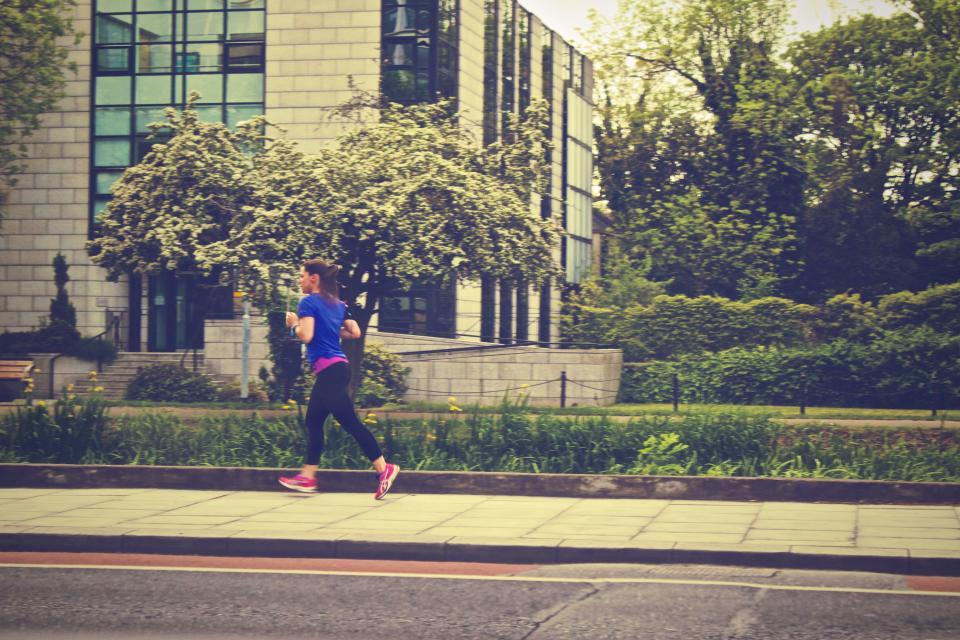 woman urban street sidewalk running runner jogging girl fitness exercise city building athlete
