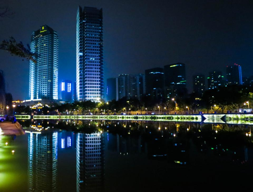 water towers skyline reflection night lights dark city china Chengdu buildings