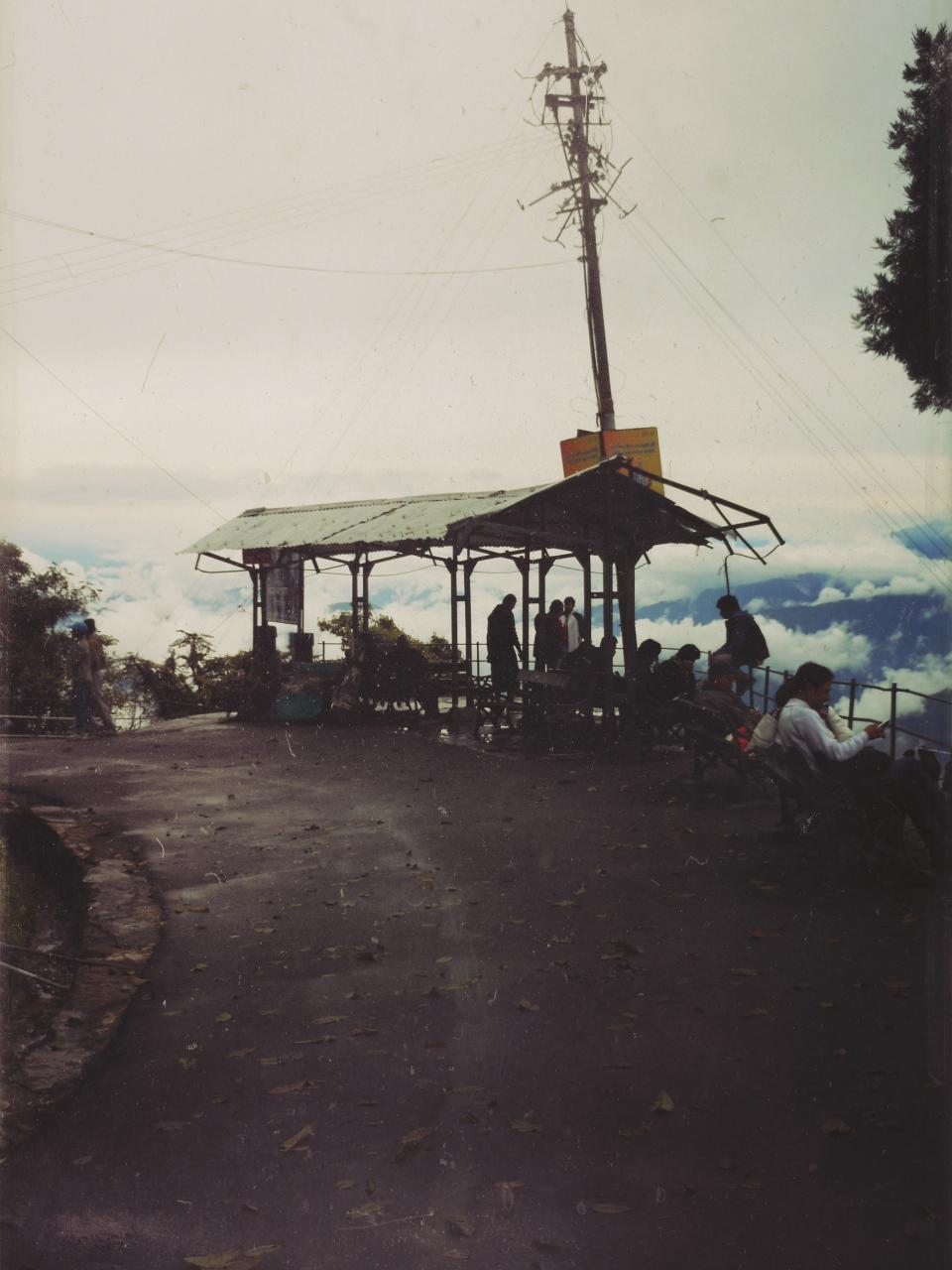 tables sky road powerlines people pavement mountains hut clouds chairs