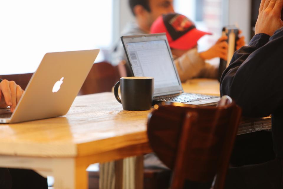 working table people mug MacBook laptops hat cup computers coffee chairs businesstechology