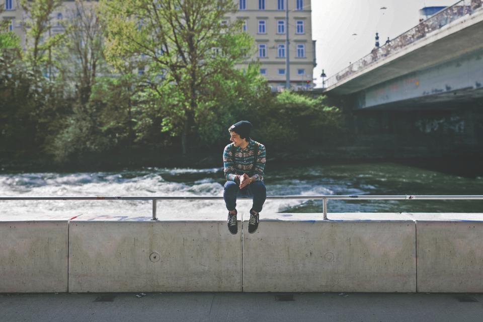water tree teenager Smile sitting shoes ledge knapsack kid jeans hat guy concrete city building Bridge boy backpack