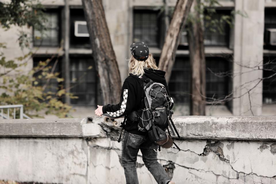 young teenager sweater skater skateboard man jeans hoodie concrete blonde black backpack
