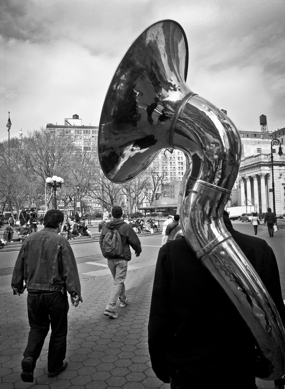 walking tuba pedestrians music lampposts instrument horn cobblestone buildlings band backpack