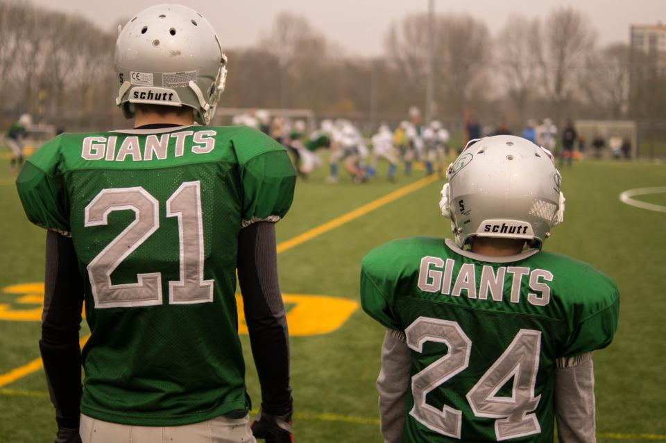 uniform teammates sports helmets green giants football field athletes