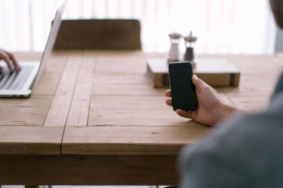 work wood technology table salt pepper meeting man MacBook laptop iphone hand chair business book