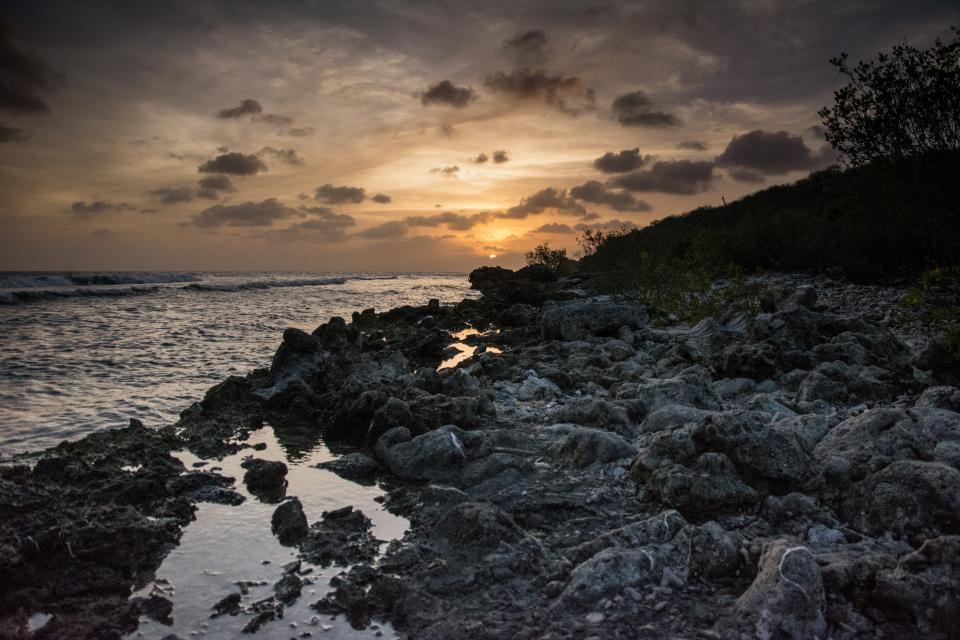 water sunset sky sea rocks ocean dusk coast clouds